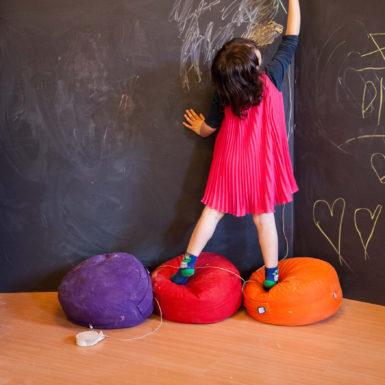 Una bambina scrive su una lavagna a tutta parete, Il mondo di Eve